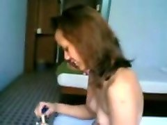 petite bodied malay girl smoking cigarette in a hotel room
